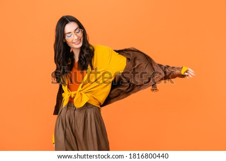 stylish woman in glasses and leather jacket standing with outstretched hand isolated on orange Royalty-Free Stock Photo #1816800440