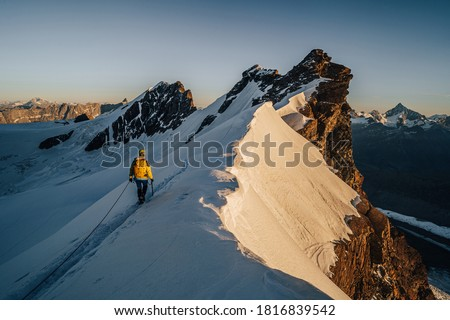 An alpinist climbing a rocky and snow mountain ridge during sunrise. Mountaineering and alpinism in Switzerland. Ascent of Breithorn, Zermatt. Alpine mountain landscape with snow and rocks. #1816839542