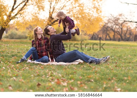 Portrait of a happy family resting in the autumn forest. Dad picks up his daughter in his arms, mom sits next to him on a blanket in an autumn park. Beautiful autumn photo session.