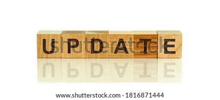 Updates, word in 3d wooden alphabet letters isolated on white background with copy space. The text is written in black letters and is reflected in the mirror surface of the table.