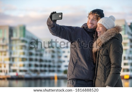 Happy tourists couple taking photo selfie on winter city travel holiday. Mobile phone outdoor lifestyle two friends walking in street. Happy Asian woman, Caucasian man on Christmas holidays.