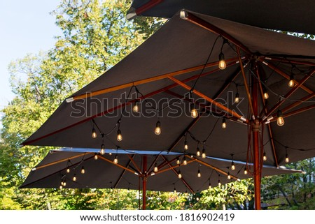 textile umbrella with a wooden frame and edison pendant lamps glowing with warm light on a backyard terrace against a background of green trees with a sky, nobody. #1816902419