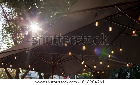 textile umbrella with a wooden frame and  pendant lamps glowing with warm light on a backyard terrace against a background of green trees and a sky with a sun glare. #1816904261