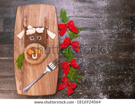 Funny food with edible symbol of 2021 bull cow made from bread, cheese and vegetables. Breakfast idea for kids. New Year Christmas food top view. Holiday, celebration, art food.