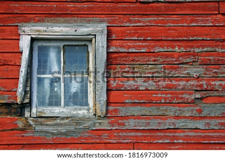 White weathered window on a red barn