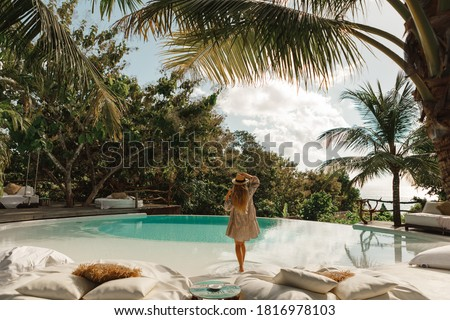 Back view  woman in summer dress and straw hat  enjoying warm sunny day near infinity pool with tropical view #1816978103
