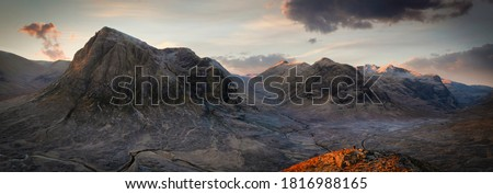 panoramic view of sunrise with tourist on mound in Glencoe, Highlands, Scotland.