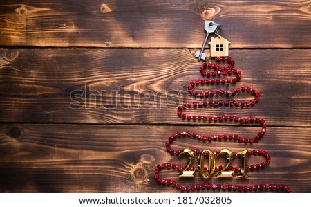 Key to the house with a keychain on top of Christmas tree made of red square beads. Flat lay on wooden background. Building or buying a house in new year. Mortgage, real estate rental. Space for text