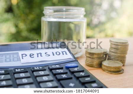 """Pension concept. Coins and calculator on a wooden table. Sticker with the word """"pension"""" #1817044091"""