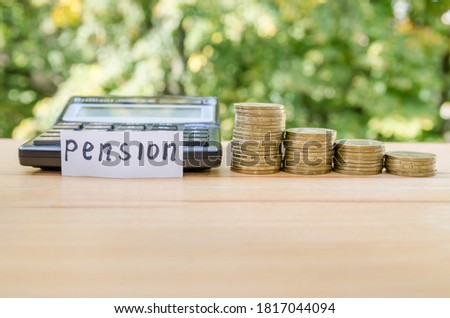 """Pension concept. Coins and calculator on a wooden table. Sticker with the word """"pension"""" #1817044094"""