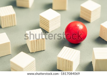 Unique red sphere in a group of sqaure cubes, small wooden objects for design and carpentry work, different and unique, positioning for advertising and business concept Royalty-Free Stock Photo #1817084069