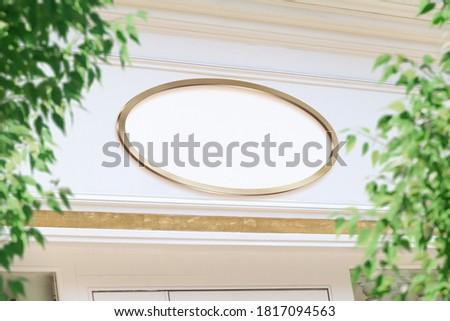 Oval storefront golden frame Mockup. Empty store brand signboard on a shop frontage