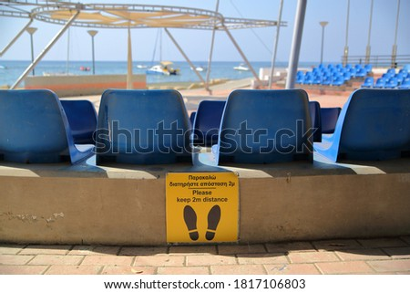 Outdoor amfitheatre with empty blue plastic seats and board text and picture keep 2 meters distance in English and Greek language, sea coast