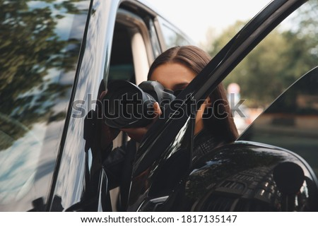 Private detective with camera spying near car outdoors Royalty-Free Stock Photo #1817135147