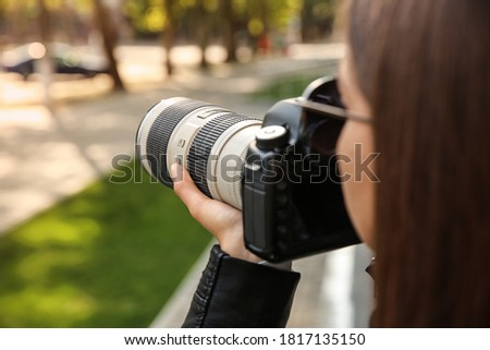 Private detective with camera spying outdoors, closeup Royalty-Free Stock Photo #1817135150