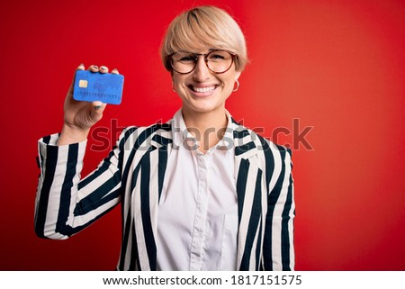 Young blonde business woman with short hair wearing glasses holding credit card with a happy face standing and smiling with a confident smile showing teeth