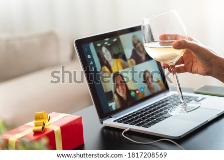 Happy woman making a toast on video call celebrating christmas with glass of wine online during coronavirus outbreak - Focus on wine glass #1817208569