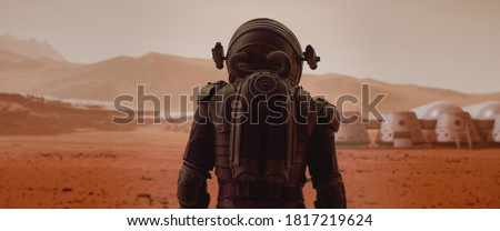 Back view of astronaut wearing space suit walking on a surface of a red planet. Martian base and rover in the background. Mars colonization concept Royalty-Free Stock Photo #1817219624