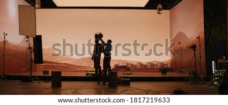 Behind the scenes shot of virtual production stage with huge LED screens, cinematorgapher shooting Mars scene. Future of movie production Royalty-Free Stock Photo #1817219633