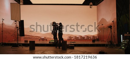 Behind the scenes shot of virtual production stage with huge LED screens, cinematorgapher shooting Mars scene. Future of movie production Royalty-Free Stock Photo #1817219636