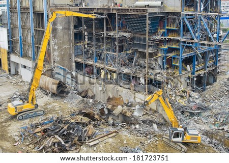Excavators working in a demolition site in front of a  big metal construction destroyed Royalty-Free Stock Photo #181723751