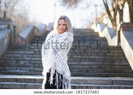 Young woman, blonde, European descent. A woman poses wrapped in a large, white lace shawl on a concrete staircase in a city park. The woman is about 21 years old. Photo taken during the cold season