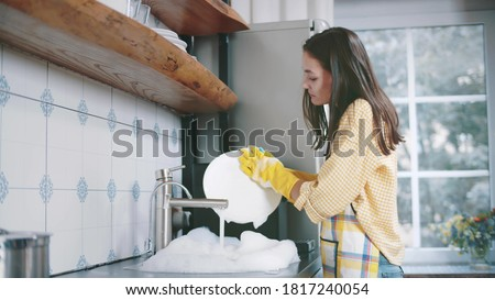 Happy attractive woman in apron and gloves washing dishes at home kitchen. Side view of pretty young housewife doing household. Beautiful female wash plates Royalty-Free Stock Photo #1817240054