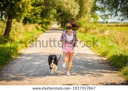 Picture of adult woman strolling with her pet and wearing a mask