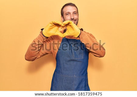 Young handsome man wearing gardener apron and gloves smiling in love doing heart symbol shape with hands. romantic concept.
