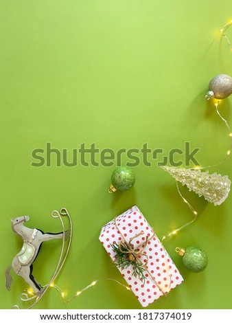 Christmas minimal composition on green background.Gift,Christmas balls, glass pine tree, rocking horse, garland. Flat lay, top view. Vertical image