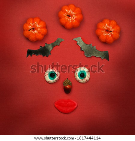Funny Halloween composition, female face made of pumpkins, paper bats