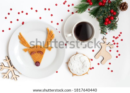 A sweet dessert of waffles and grapes with a picture of a deer on a plate, a cup of coffee, and a white cake on a white table with a sprig of spruce and New Year's wooden toys snowflake, deer
