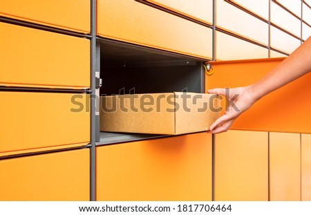 Post automat terminal and hand with parcel Royalty-Free Stock Photo #1817706464