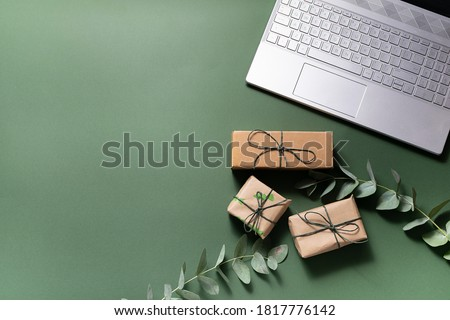 Online holiday shopping concept. Lap top, gift boxes and eucalyptus twigs on deep green background. #1817776142