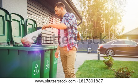 Caucasian Man is Throwing Away Two Plastic Bags of Trash next to His House. One Garbage Bag is Sorted with Biological Food Waste, Other with Recyclable Bottles Garbage Bin. Royalty-Free Stock Photo #1817801867