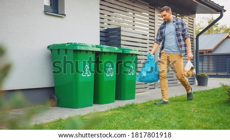 Caucasian Man is Walking Outside His House in Order to Take Out Two Plastic Bags of Trash. One Garbage Bag is Sorted as Biological Food Waste, Other is Recyclable Bottles Garbage Bin. Royalty-Free Stock Photo #1817801918