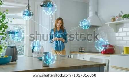 Internet of Things Concept: Young Woman Using Smartphone in Kitchen. She controls her Kitchen Appliances with IOT. Graphics Showing Digitalization Visualization of Connected Home Electronics Devices Royalty-Free Stock Photo #1817816858