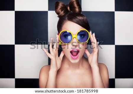 Attractive surprised young woman wearing sunglasses on checkered background, beauty and fashion concept #181785998