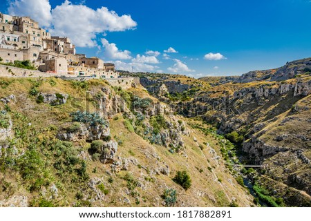 Matera, Basilicata, Italy - Panoramic view from the top of the Sassi of Matera, Barisano and Caveoso. The ancient houses of stone and brick, carved into the rock. The ravine in the background. #1817882891