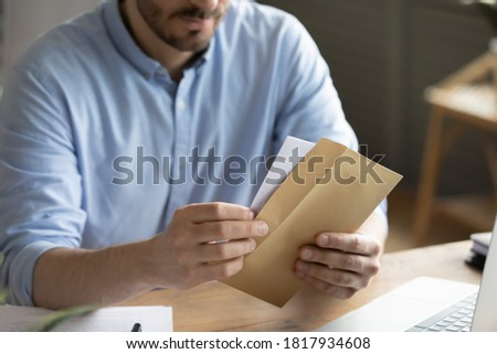 Crop close up of man sit at desk open envelope with paper letter or correspondence at office. Male worker get postal paperwork or notice notification at workplace, receive message or invitation. Royalty-Free Stock Photo #1817934608