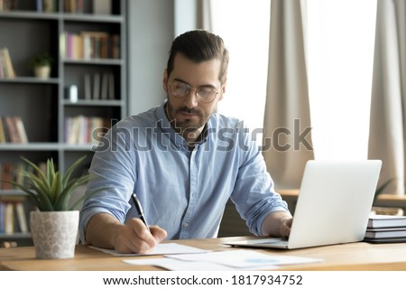 Concentrated young caucasian man in glasses sit at desk work on computer make notes. Focused serious male worker or freelancer busy at home office watch webinar on laptop, handwrite on paper. Royalty-Free Stock Photo #1817934752