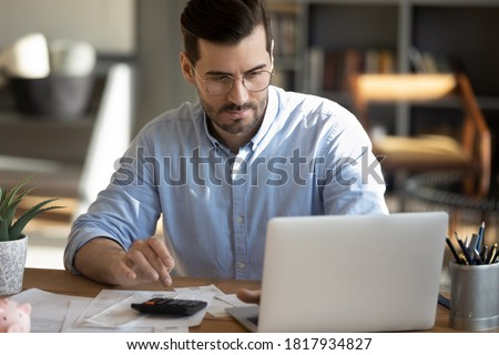 Focused young Caucasian man look at laptop screen calculate expenses expenditures pay bills taxes online. Millennial male busy managing household family budget, take care of financial paperwork. Royalty-Free Stock Photo #1817934827