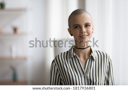 Profile picture of millennial caucasian artistic hairless girl look at camera posing at home. Headshot portrait of smiling young creative bald shaved hair woman artist or designer show confidence.