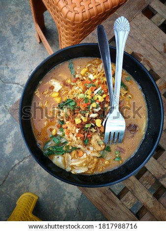 instant noodles. fast food. with chives. egg mixture. spoon and fork. Central Asian cuisine. Horizontal orientation. against the backdrop of tables and chairs