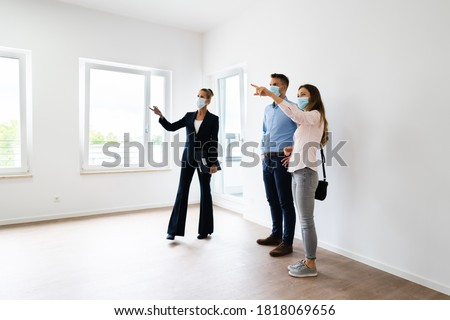 Happy Couple Buying New Home With Realtor Wearing Face Masks Royalty-Free Stock Photo #1818069656