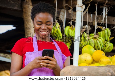 a young beautiful african market woman feeling happy about what she saw on her cellphone Royalty-Free Stock Photo #1818084425