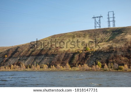 Autumn landscape, river, energy pillars, High voltage pole on blue sky background #1818147731