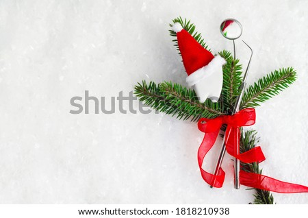 mirror and probe, dental instruments with red ribbon for new year on fir, tooth in santa hat on snow. Creative medical christmas stomatology winter background. Health care, hygiene concept. Copy space #1818210938