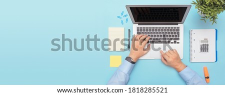 Workspace with laptop, office supplies. Man working on stylish table desk. Image with copy space on blue background