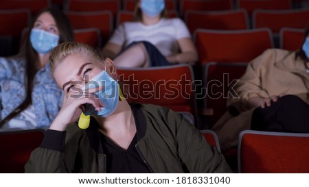 People in masks watch funny movie. Media. People in medical masks sit in movie theater and laugh while watching movie. Opening of cinemas during pandemic coronavirus #1818331040